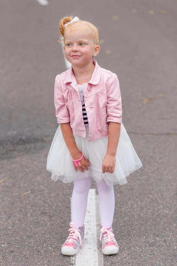 Download A Cute Little Girl In A Beautiful Dress And Sneakers Playing On Stock Photo - Image: 83720978