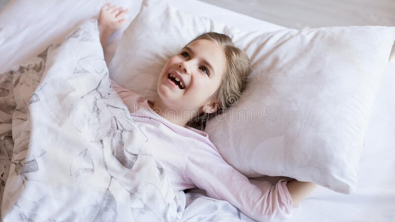 Cute little girl in bed woke up in the morning stock photo