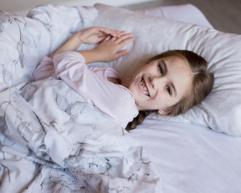 Cute little girl in bed woke up in the morning royalty free stock photography