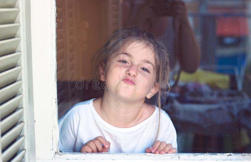 Cute little girl behind the window, making faces, being boring stock photo