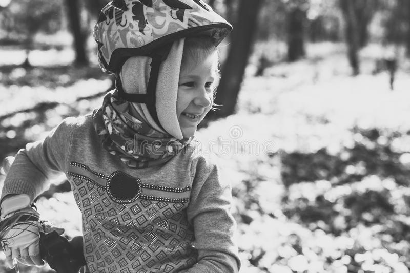 Cute little girl with a bicycle in the autumn forest stock photography