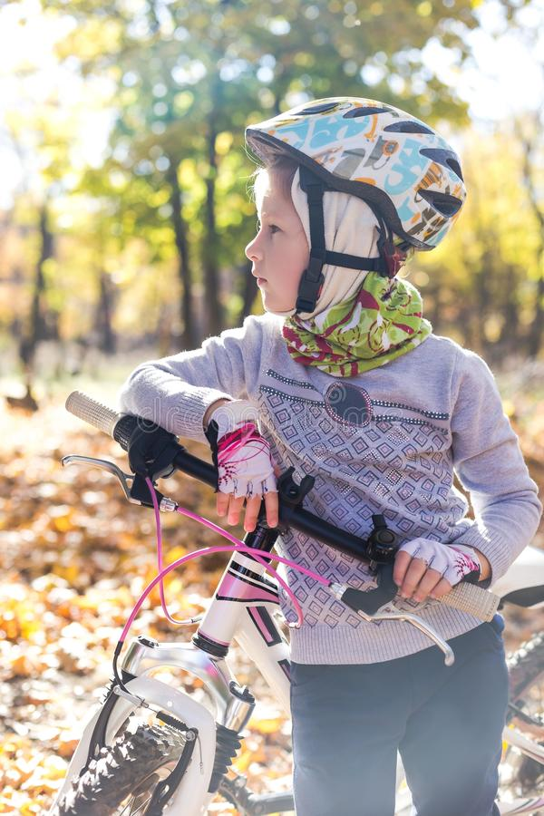 Cute little girl with a bicycle in the autumn forest royalty free stock photography
