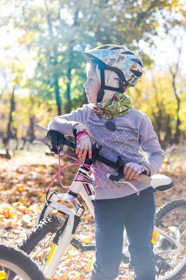 Cute little girl with a bicycle in the autumn forest stock photos