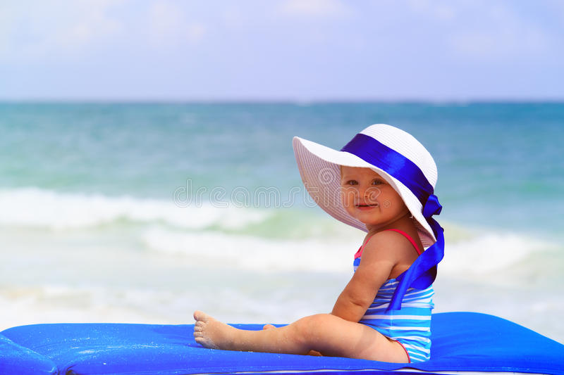 Cute little girl in big hat on summer beach royalty free stock images