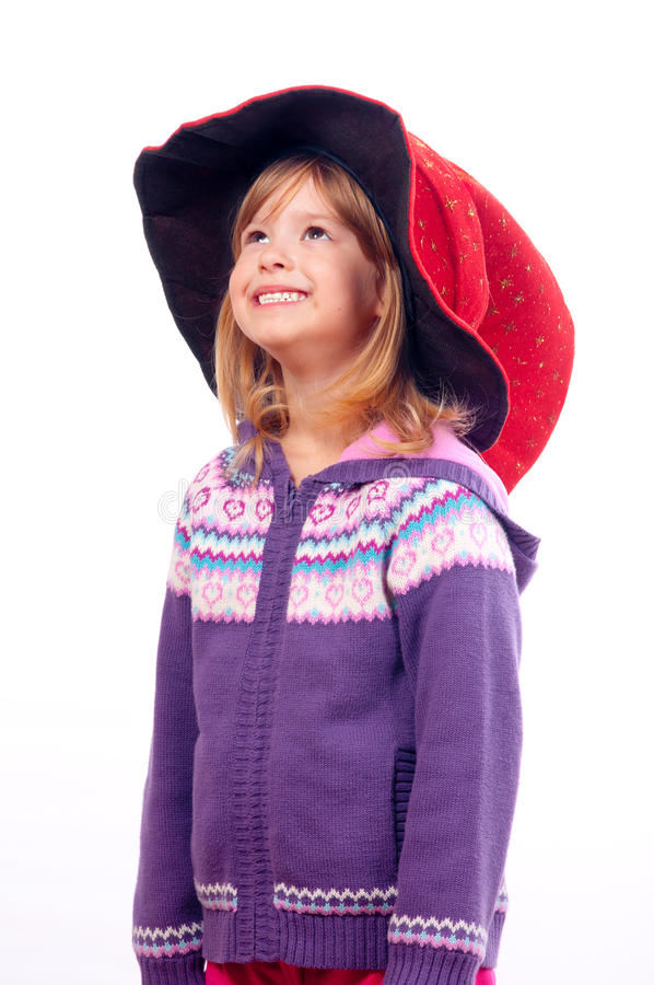 Cute little girl with big red wizards hat smiling royalty free stock photography