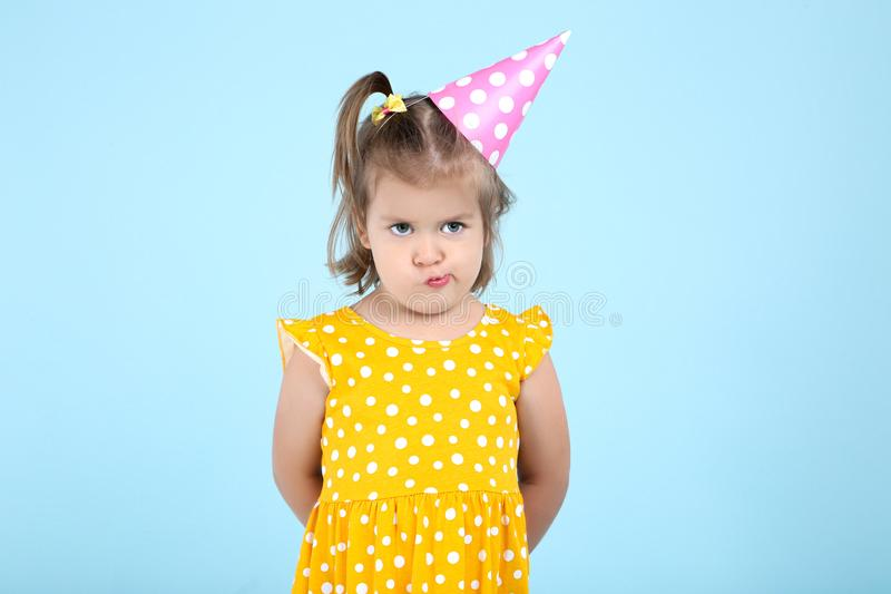 Cute little girl in birthday cap. On blue background stock photography
