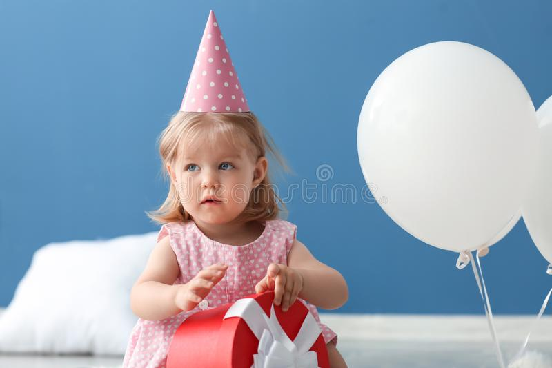 Cute little girl in birthday party cap with gift box sitting on floor indoors royalty free stock photography