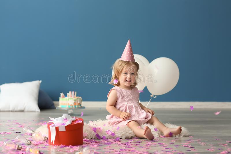 Cute little girl in birthday party cap with gift box sitting on furry rug indoors royalty free stock images