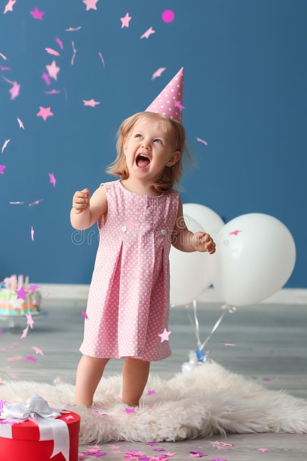 Cute little girl in birthday party cap playing with paper confetti indoors royalty free stock image