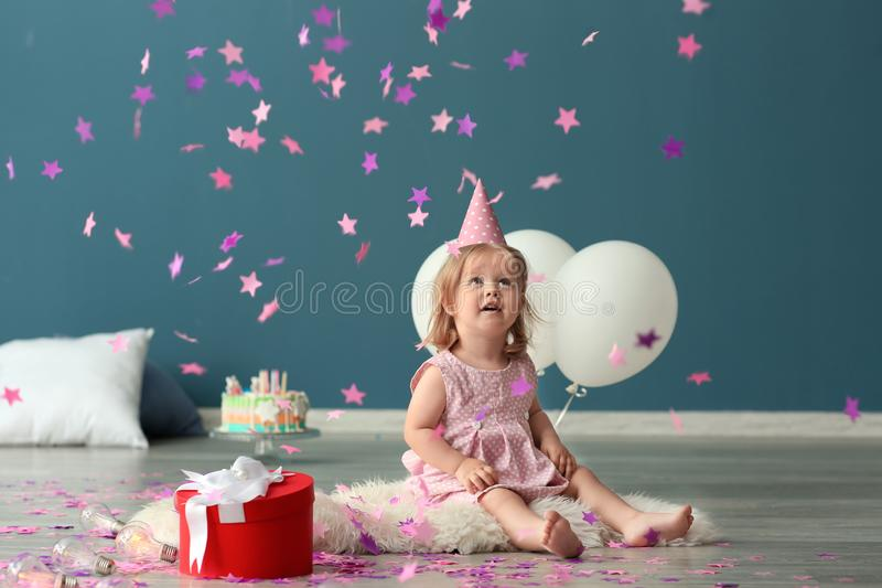Cute little girl in birthday party cap playing with paper confetti indoors stock photo