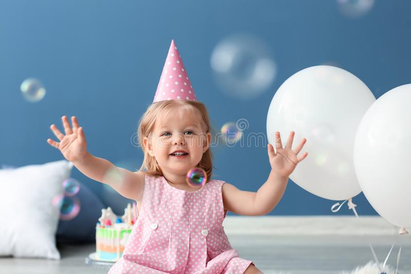 Cute little girl in birthday party cap sitting on floor indoors stock photo