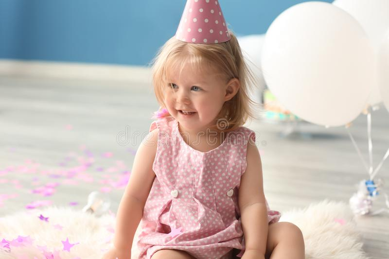 Cute little girl in birthday party cap sitting on furry rug indoors royalty free stock photography