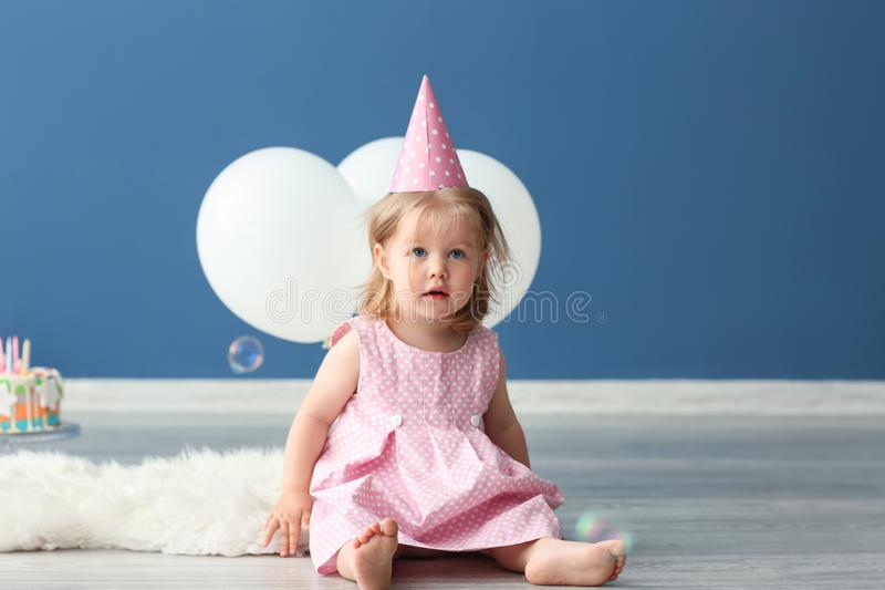 Cute little girl in birthday party cap sitting on rug indoors stock images