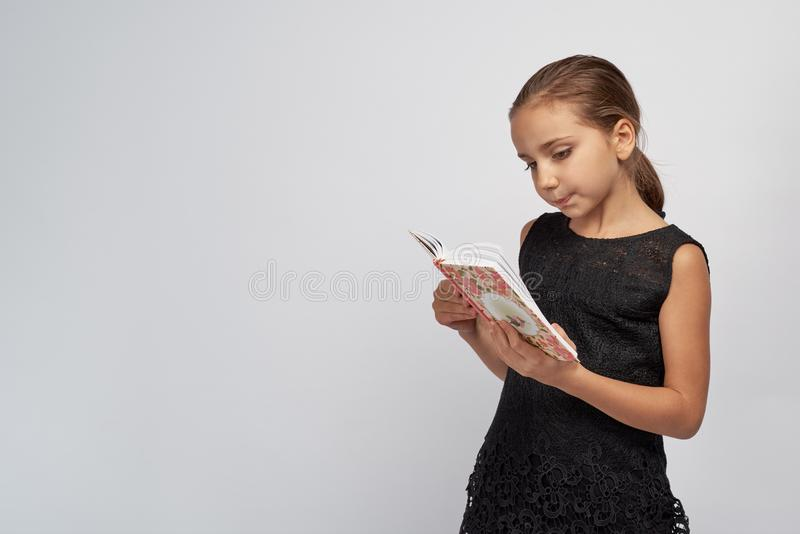 Cute little girl in a black dress with passionate pensive expression reading a book stock photos
