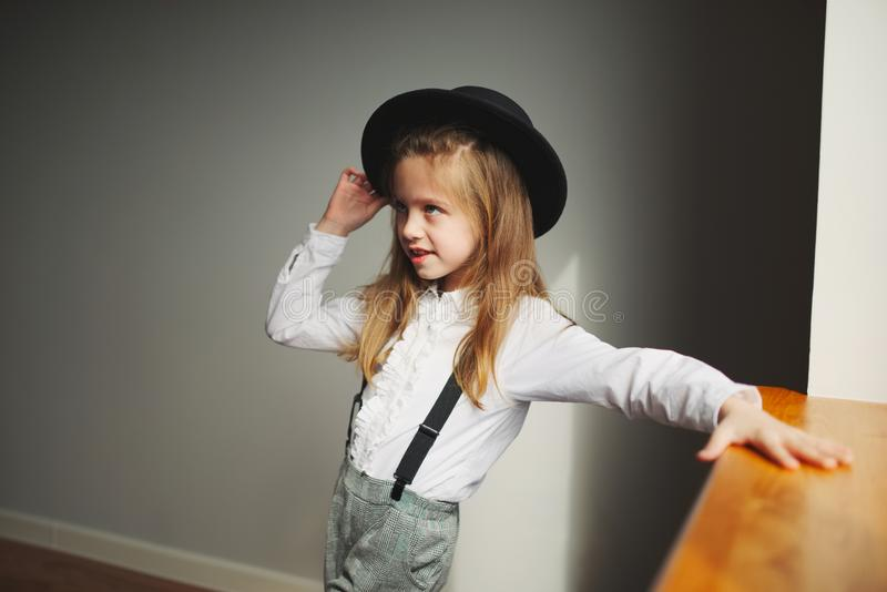 Cute little girl with black hat at home stock photo