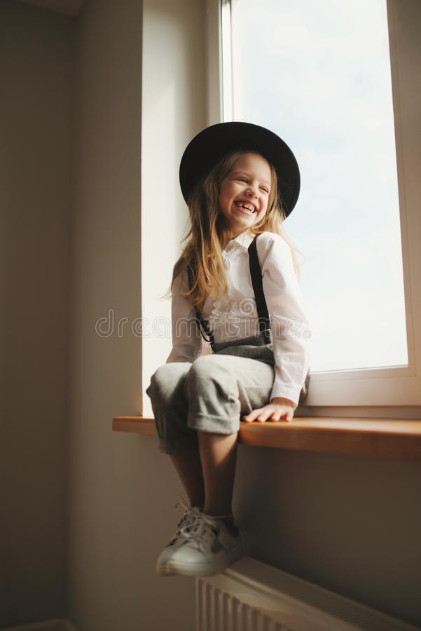 Cute little girl with black hat at home royalty free stock image