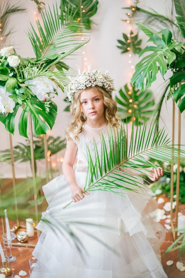 Cute little girl with blond curly hair in a white wedding dress and a wreath of flowers in floral decorations stock photography