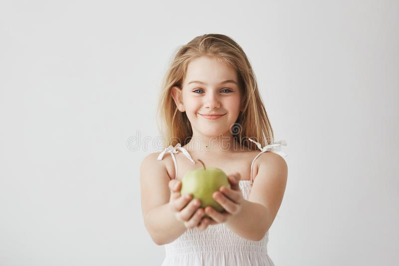 Cute little girl with blond long hair and blue eyes in white dress smiling brightfully, holding apple in hands and stock photos