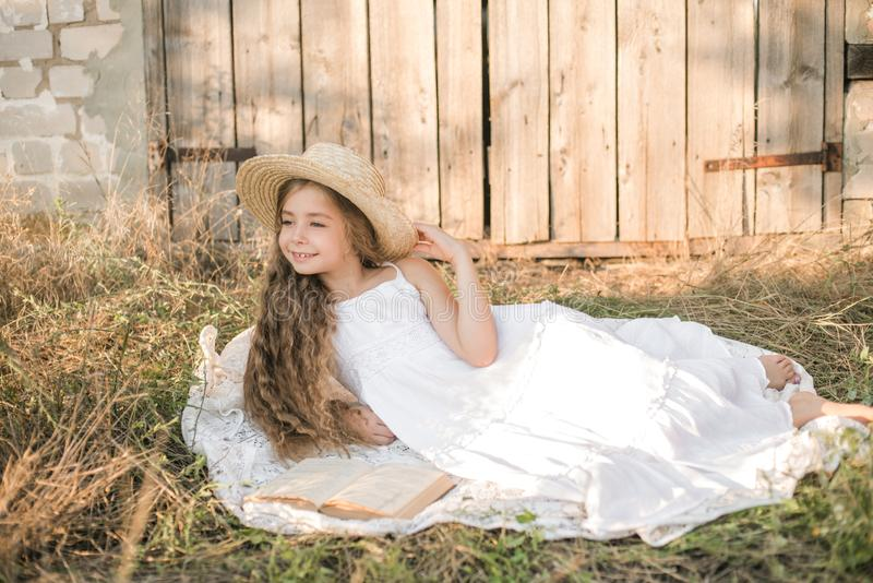 Cute little girl with blond long hair in a summer field at sunset with a white dress with a straw hat royalty free stock photo