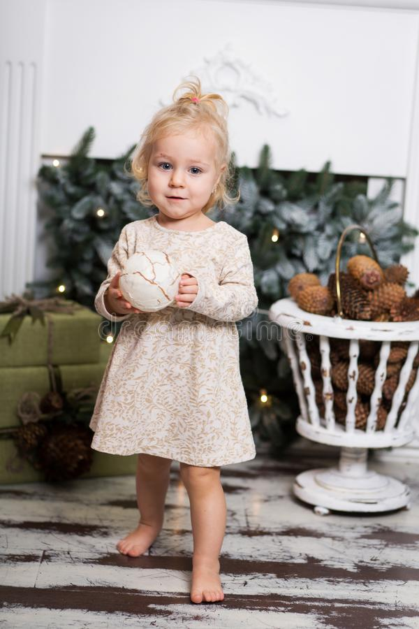 Cute little girl with blonde hair decorating christmas tree royalty free stock images