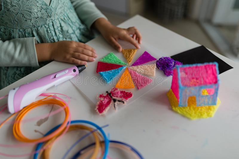 Cute little girl makes a plastic house, draws parts with a 3D pen. STEM and STEAM education. Development, modeling, education, royalty free stock images
