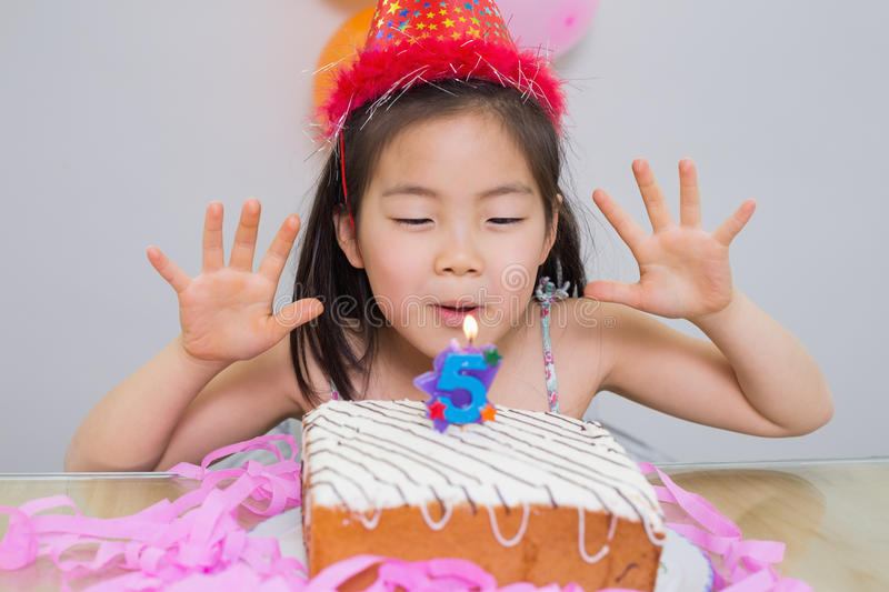 Cute little girl blowing her birthday cake. Closeup of a cute little girl blowing her birthday cake royalty free stock image