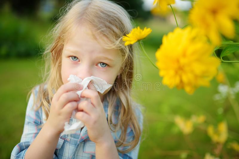 Cute little girl blowing her nose by beautiful yellow coneflowers on summer day. Allergy and asthma issues in small kids. royalty free stock images