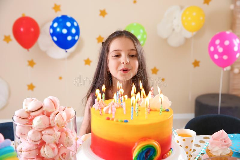 Cute little girl blowing out candles on her birthday cake royalty free stock photography