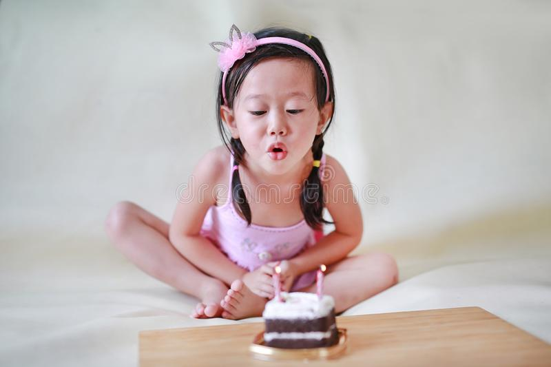 Cute little girl blowing small birthday candles, 2 years old kid celebrating stock images