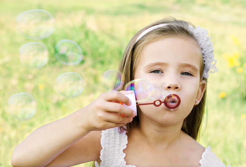 Cute little girl is blowing a soap bubbles royalty free stock photos