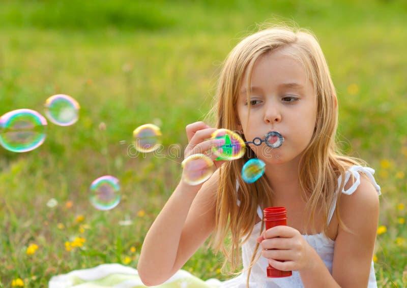Cute little girl blowing soap bubbles on meadow stock photo