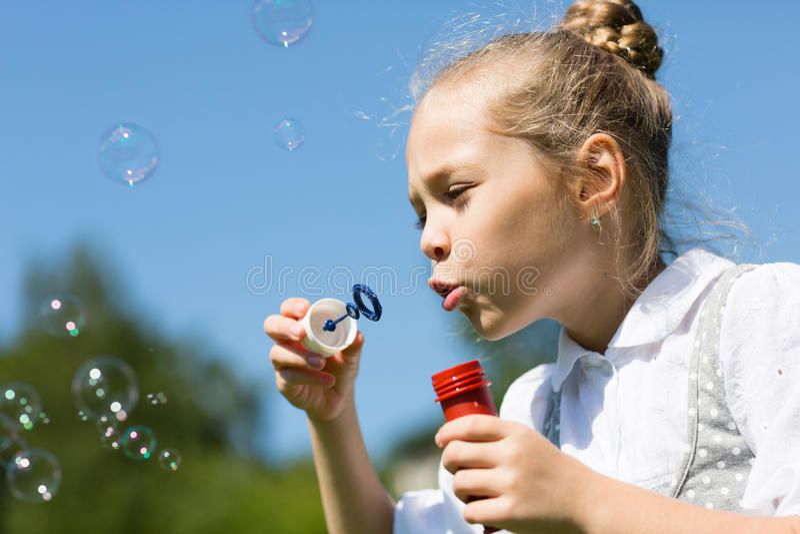 Cute little girl blowing soap bubbles stock photos