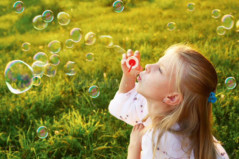 Cute little girl blowing soap bubbles on a summer day in the eve stock images
