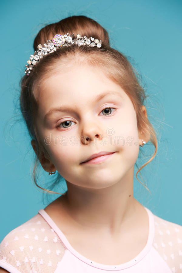 Cute little girl on a blue background close-up stock photography