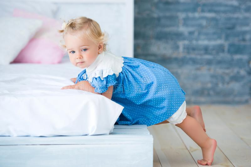 Cute little girl in blue dress lying on the bed in the interior. Bedtime royalty free stock image