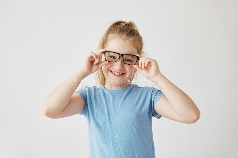 Cute little girl with blue eyes and light hair smiles brightfully, plays with mom taking her glasses and trying them on stock photography