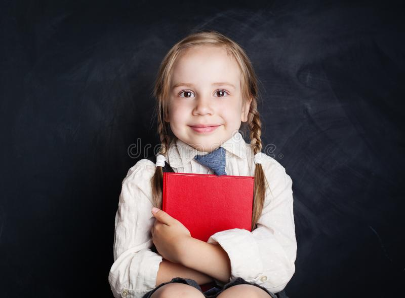 Cute little girl with book. Happy Child on empty blackboard. Background with copy space royalty free stock images