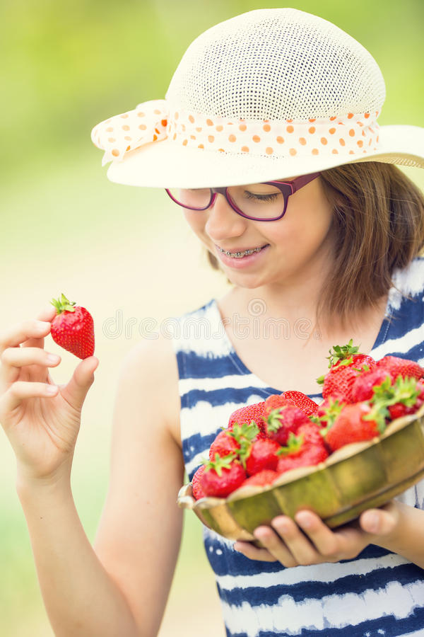 Cute little girl with bowl full of fresh strawberries. Pre - teen girl with glasses and teeth - dental braces stock photography