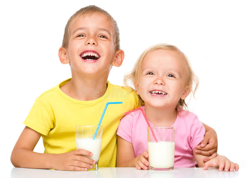 Cute little girl and boy are drinking milk. Using straw, isolated over white stock photos