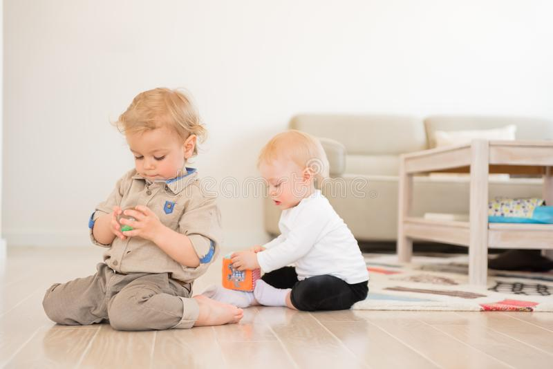 Cute little girl and boy playing with toys at home stock image