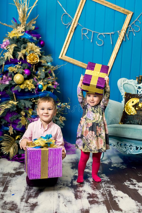 Cute little girl and boy are smiling and holding gifts under the Christmas tree. Brother and sister unpack gift boxes on Christmas royalty free stock photos