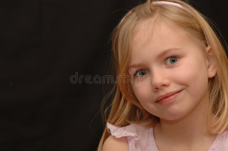 Cute Little Girl with Bright Eyes. Portrait of a cute little 5-year old girl in a pink outfit with big, bright blue eyes royalty free stock photography