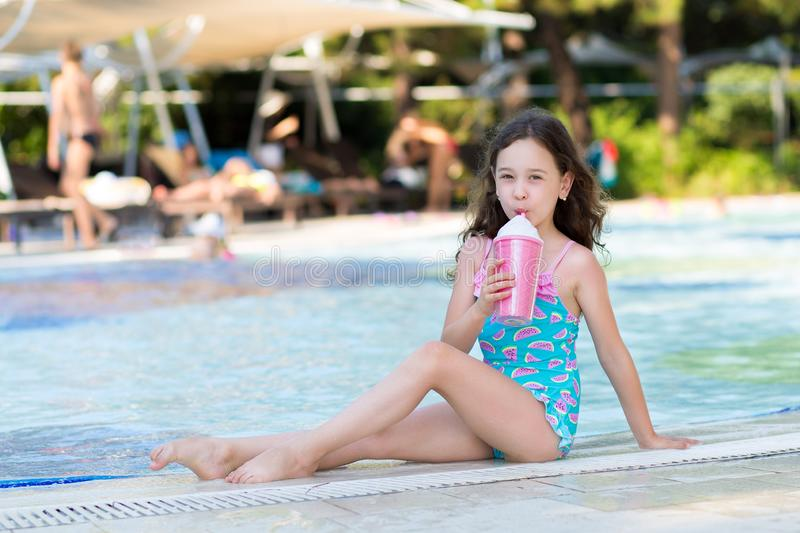 Cute little girl in bright swimsuit sitting with a cocktail by the pool on sunny summer day. Family vacation concept stock image