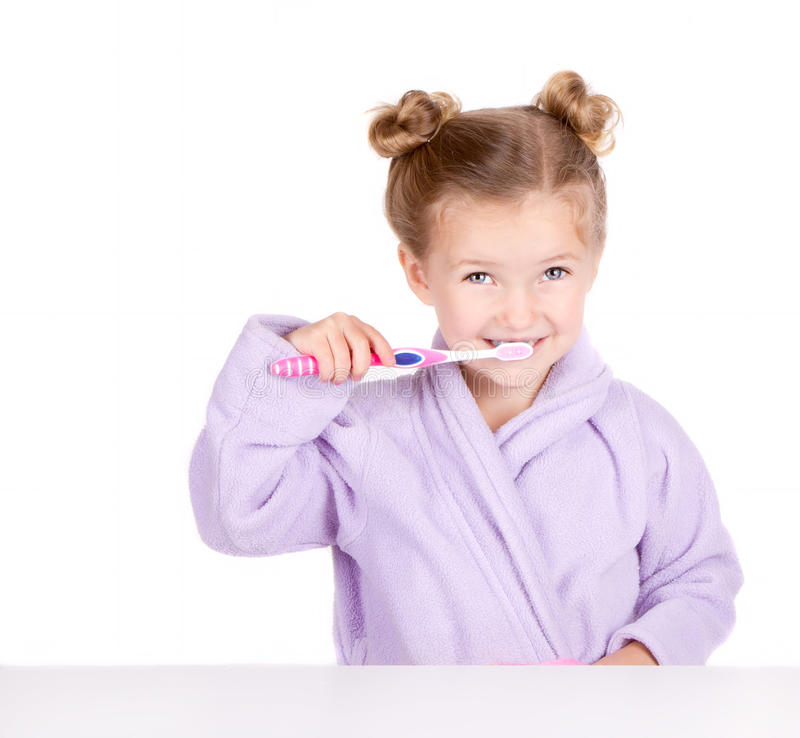 Cute little girl brushing teeth. In bathrobe isolated on white royalty free stock photography