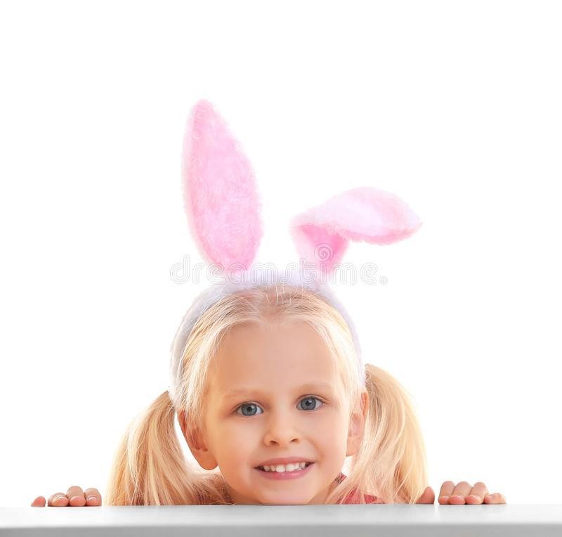 Cute little girl with bunny ears and basket full of Easter eggs on background stock image