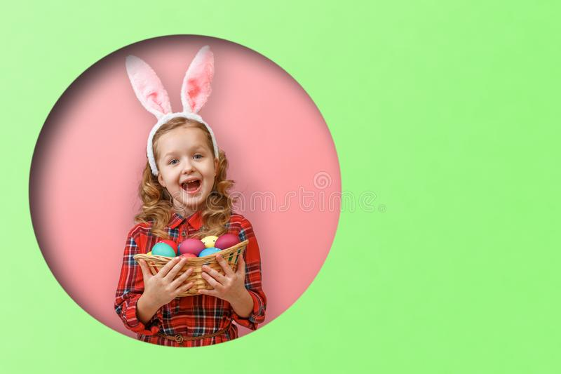 Cute little girl with bunny ears holding basket of Easter eggs. Kid in a round hole circle in colored green and pink backgrounds.  royalty free stock images