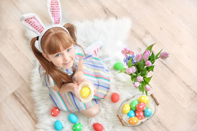 Cute little girl with bunny ears holding bright Easter egg. In decorative nest, indoors stock images