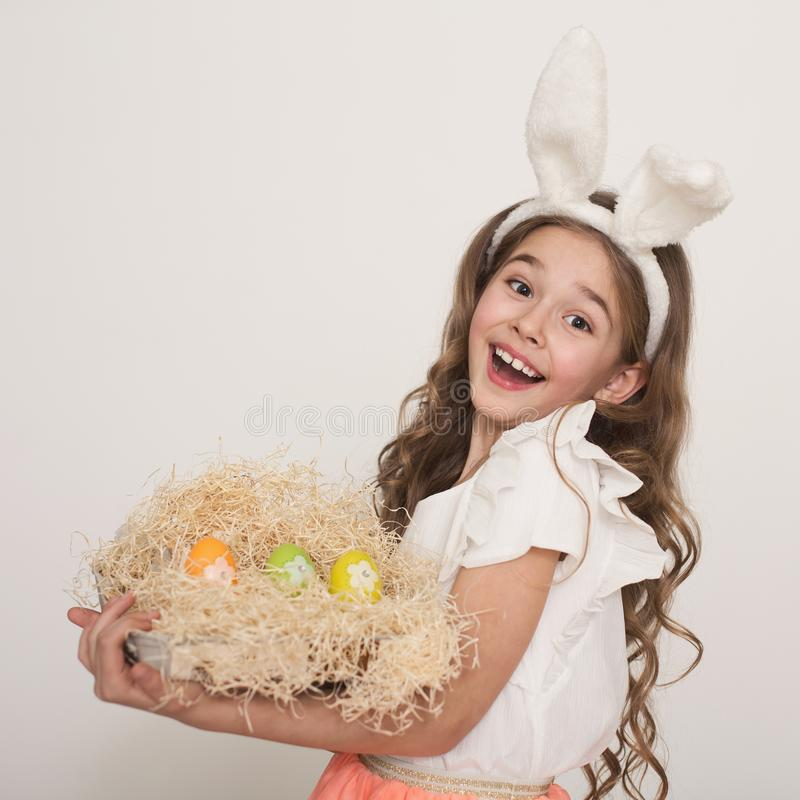 Cute little girl with bunny ears holding bright Easter eggs stock images