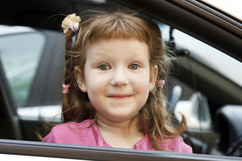 Cute little girl in a car royalty free stock images