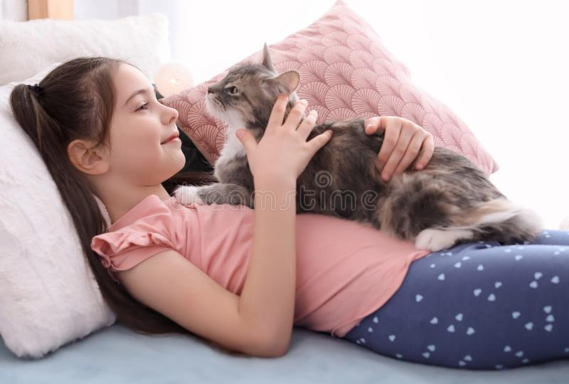 Cute little girl with cat lying on bed. At home stock photo